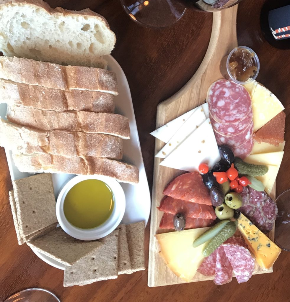 cheese board laid out with selection of meats and bread on a platter