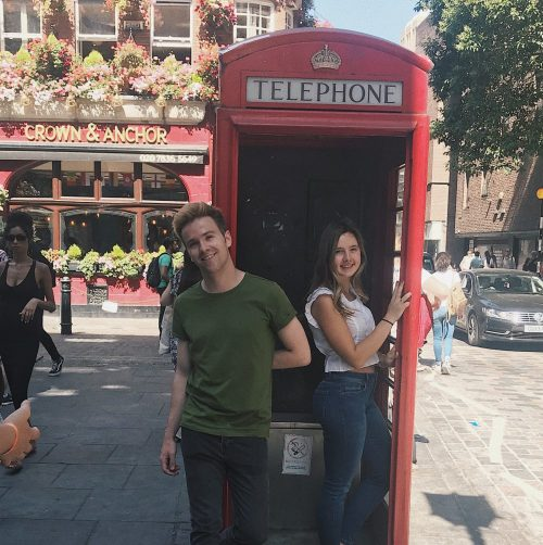 London intern posing in a phone booth with partner