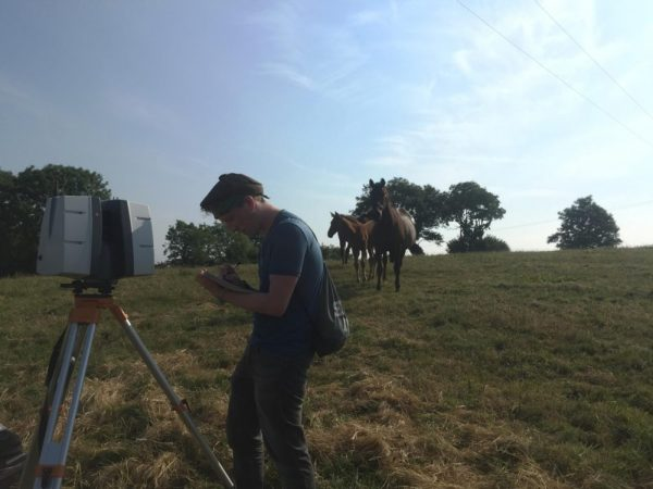 Archaeology interns working in the field with a Lidar scanner
